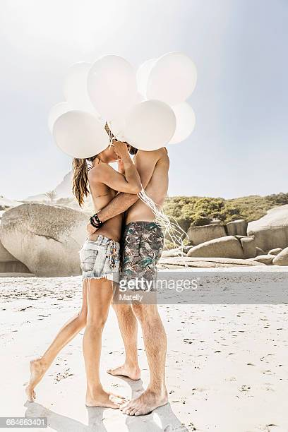 Couple holding bunch of balloons kissing on beach, Cape Town, South Africa