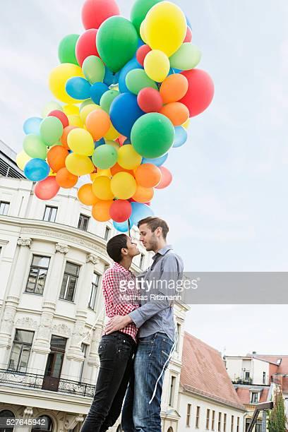 Couple holding bunch of colorful balloons