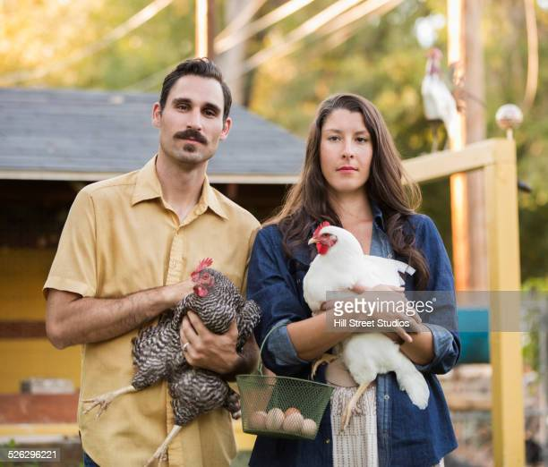 Couple holding chickens and eggs outside coop