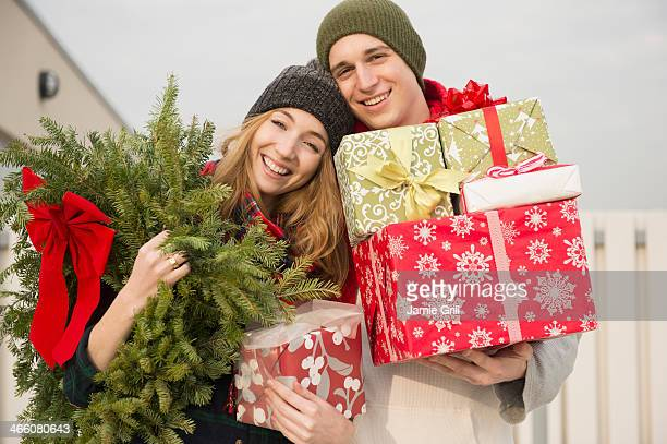 couple holding christmas presents and wreath - heterosexual couple stock pictures, royalty-free photos & images
