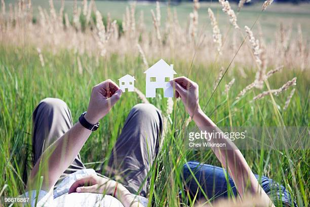 Couple holding cut-out paper houses