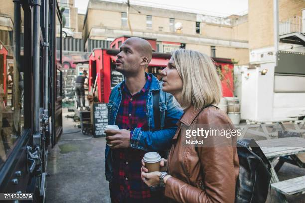 Couple holding disposable coffee shop standing outside store