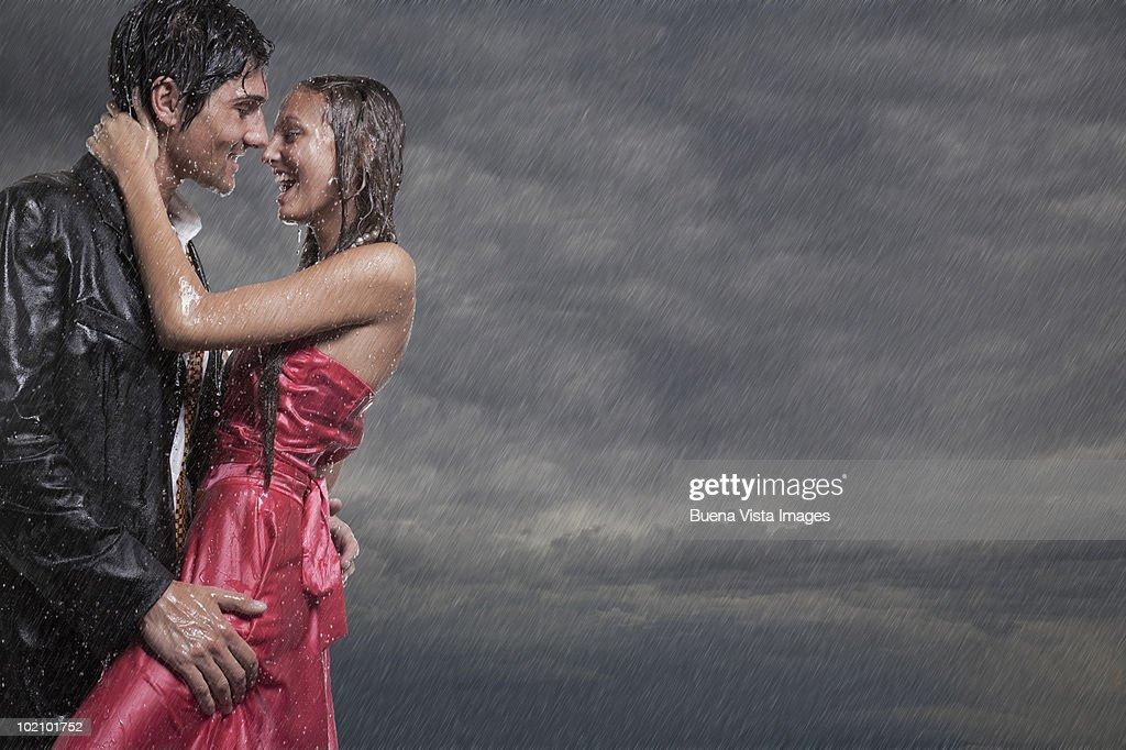 Couple holding each other in rainstorm : Bildbanksbilder