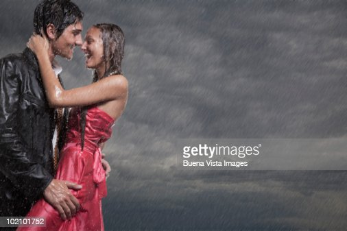 Couple Holding Each Other In Rainstorm High-Res Stock