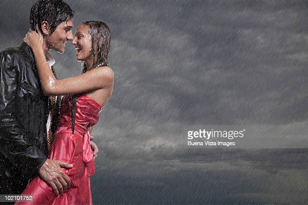 Couple holding each other in rainstorm