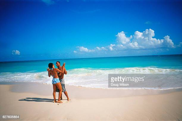 couple holding each other on a beach - bermuda stock pictures, royalty-free photos & images