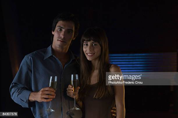Couple holding glasses of champagne, smiling at camera, portrait