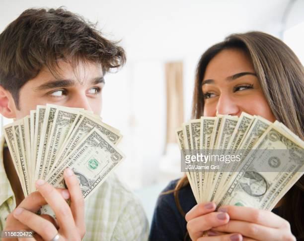 couple holding handfuls of money - fund fair stockfoto's en -beelden