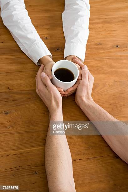 A couple holding hands across a table