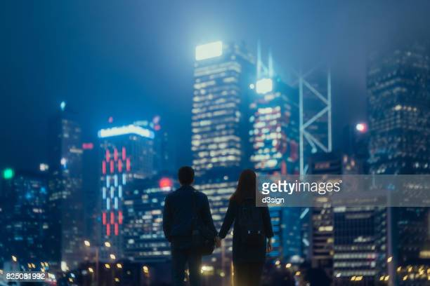 Couple holding hands against illuminated urban cityscape at night