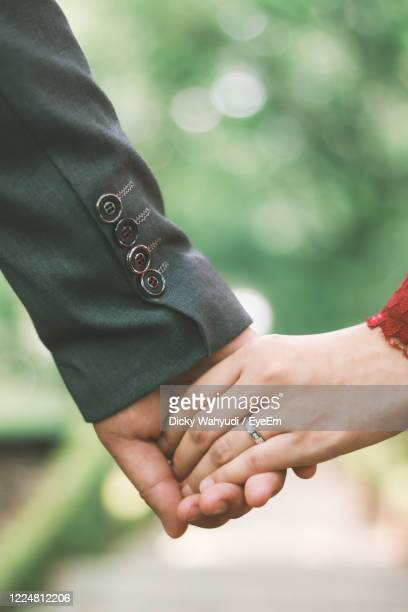 couple holding hands against trees - 袖 ストックフォトと画像