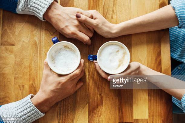 Couple holding hands and coffee cups at cafe table