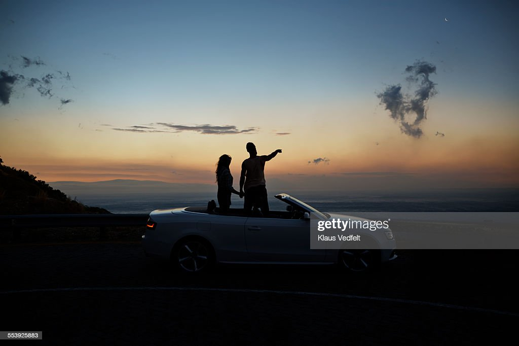 Couple holding hands and looking at sunset : Foto de stock