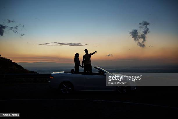 Couple holding hands and looking at sunset
