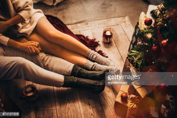 couple holding hands and relaxing sitting under christmas tree - amore foto e immagini stock