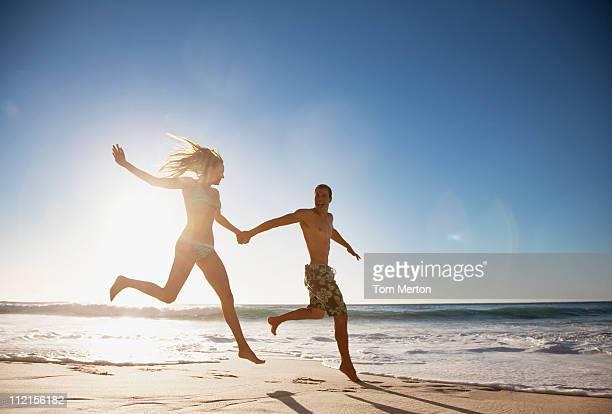 Couple tenant les mains et courir sur la plage