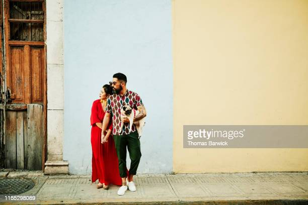 Couple holding hands and standing in front of colorful wall