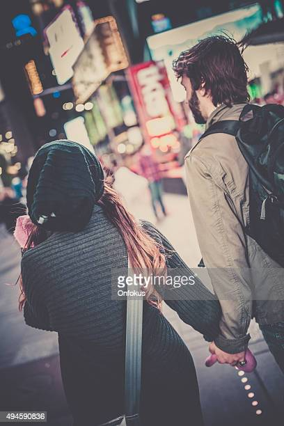 Couple Holding Hands and Walking in Time Square, NYC