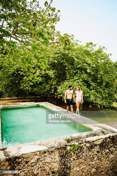 Couple holding hands and walking on edge of plunge pool at tropical luxury resort