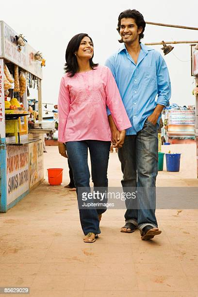 Couple holding hands and walking past food stalls, India