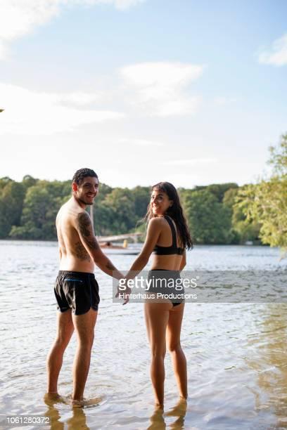 couple holding hands at lake together - oben ohne frau stock-fotos und bilder