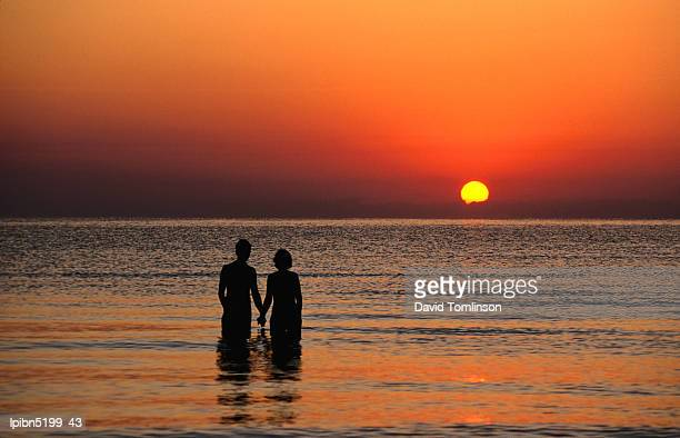 Couple holding hands at sunset over the Bay of Alcudia., Mallorca, Balearic Islands, Spain, Europe