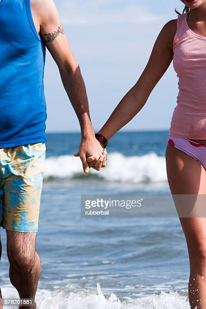 couple holding hands at the beach - copulation of humans stock photos and pictures