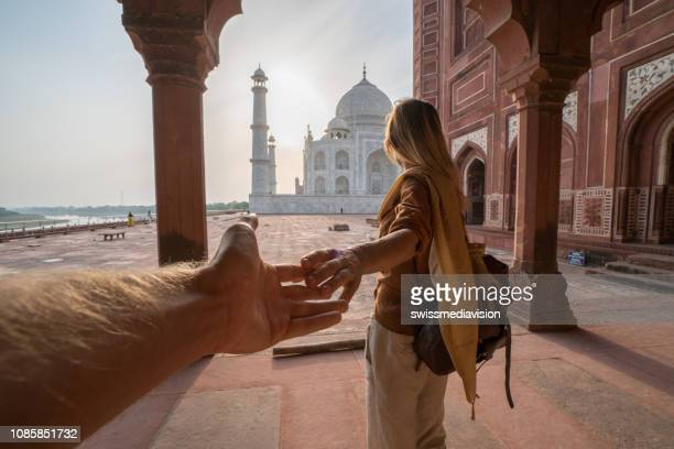 couple holding hands at the taj mahal, india - following stock pictures, royalty-free photos & images