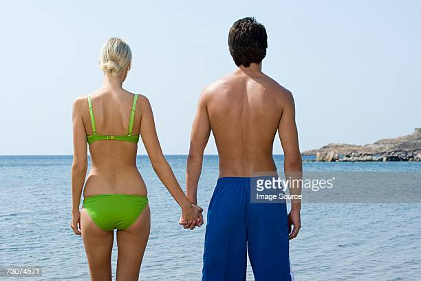 couple holding hands by the sea - heterosexual couple stock pictures, royalty-free photos & images