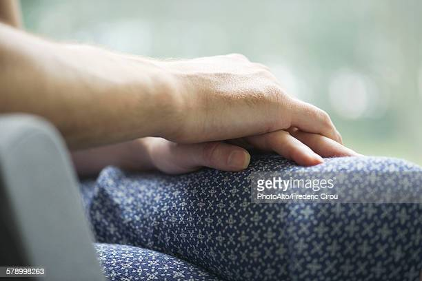 Couple holding hands, close-up