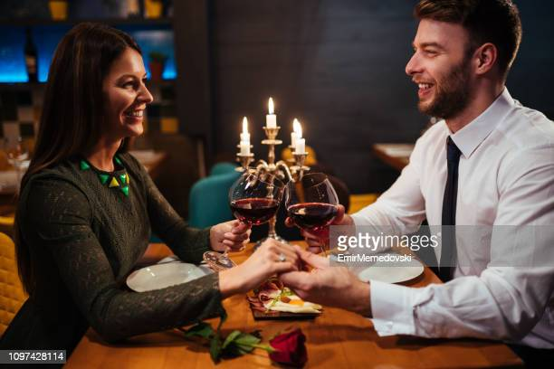 Couple holding hands during romantic dinner in a restaurant