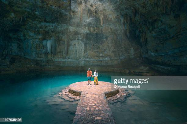 couple holding hands exploring a cenote in yucatan peninsula, mexico - wereldreis stockfoto's en -beelden