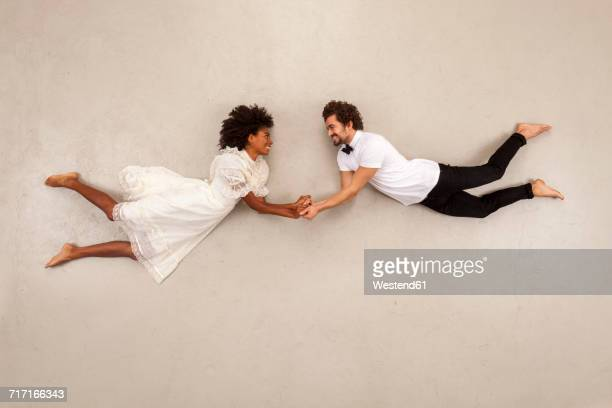 couple holding hands, falling in love - beige background stock pictures, royalty-free photos & images