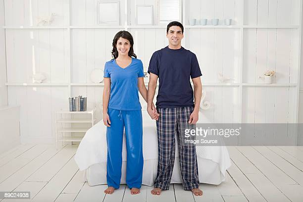 couple holding hands in a bedroom - pajamas stock pictures, royalty-free photos & images