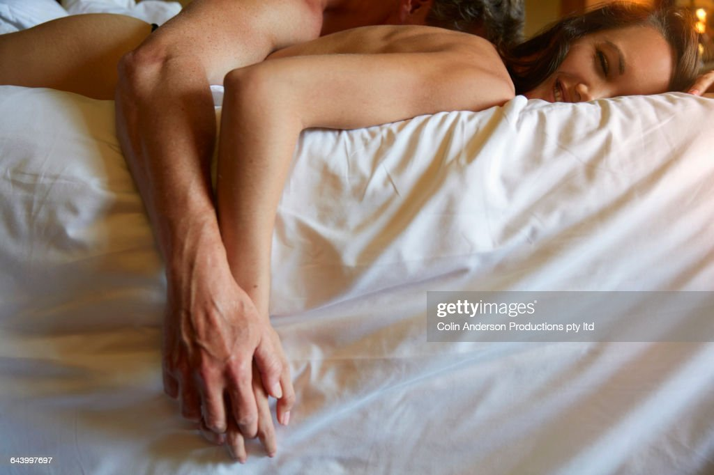Couple holding hands in bed : Stock Photo
