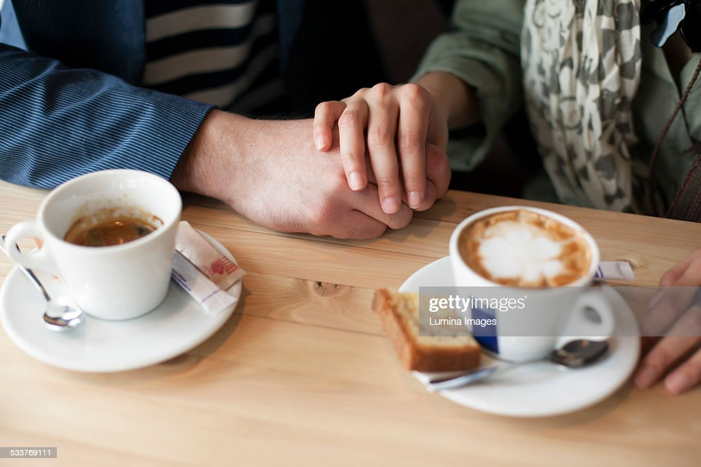 Couple holding hands in cafe : Foto stock