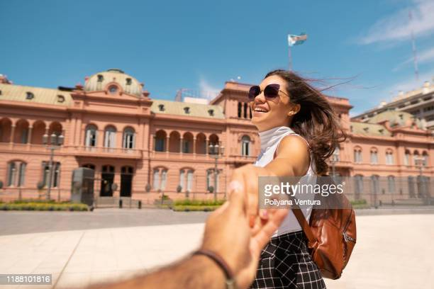 couple holding hands in front of casa rosada in buenos aires - buenos aires stock pictures, royalty-free photos & images