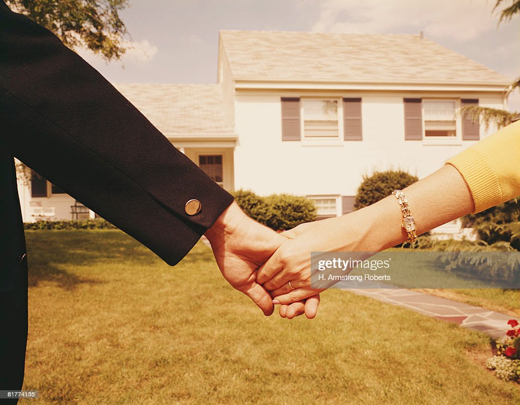 Couple holding hands in front of house. (Photo by H. Armstrong Roberts/Retrofile/Getty Images) : Bildbanksbilder
