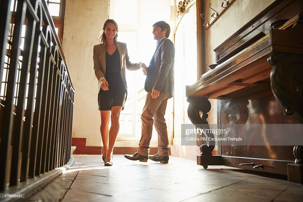Couple holding hands in hotel lobby : Stock Photo