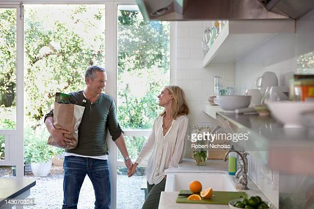 couple holding hands in kitchen - dreiviertelansicht stock-fotos und bilder