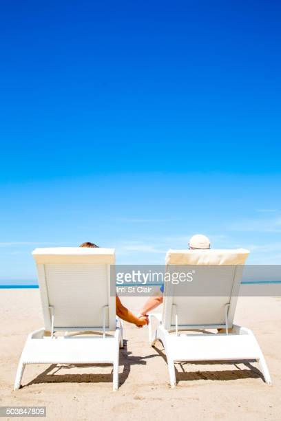 Couple holding hands in lounge chairs on beach