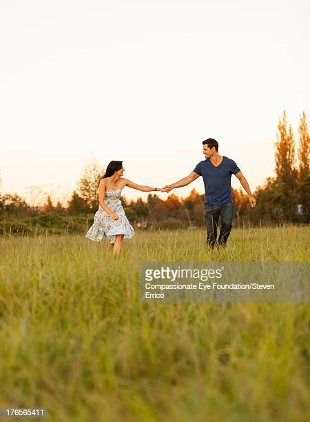 couple holding hands in meadow - cef do not delete stock pictures, royalty-free photos & images