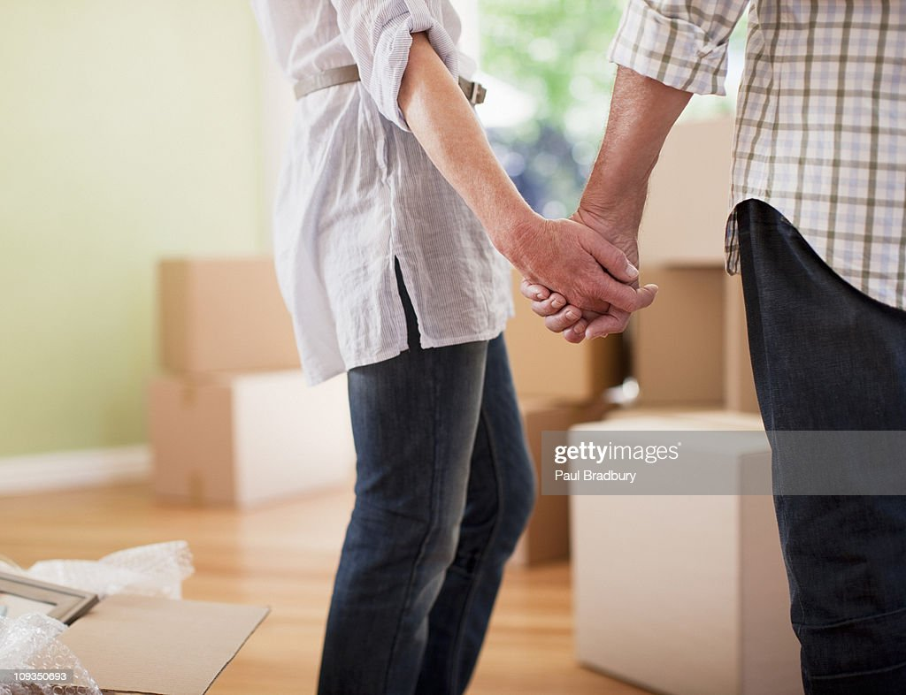 Couple holding hands in new house : Stock Photo