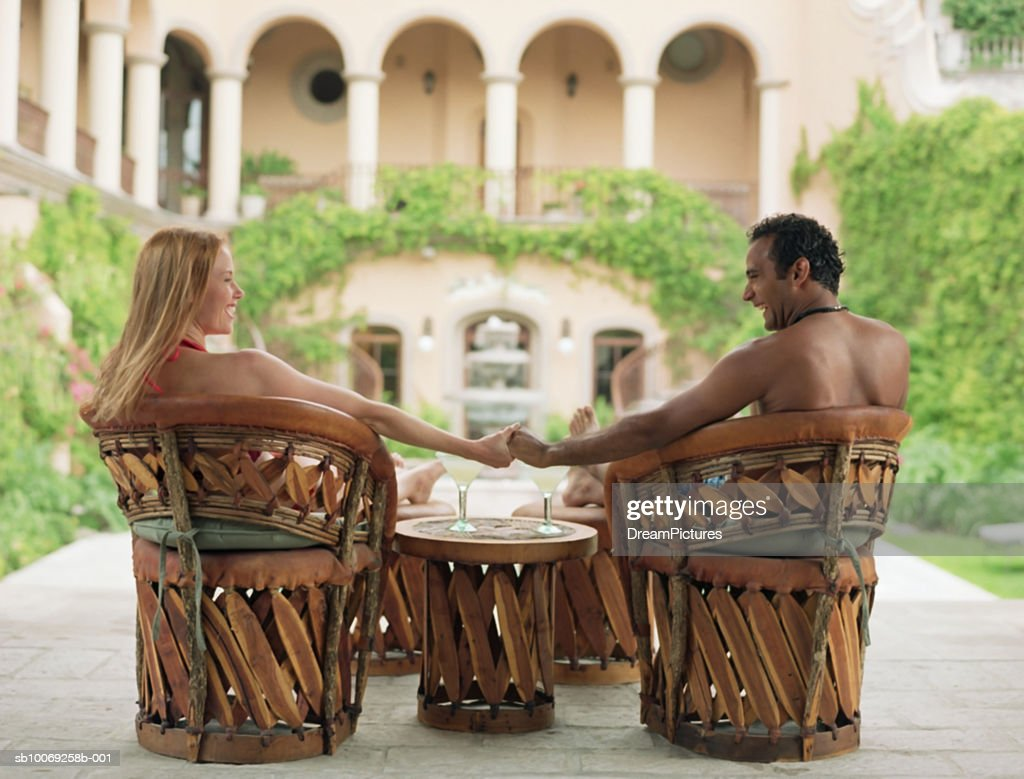 Couple holding hands in outdoor patio chairs : Stockfoto