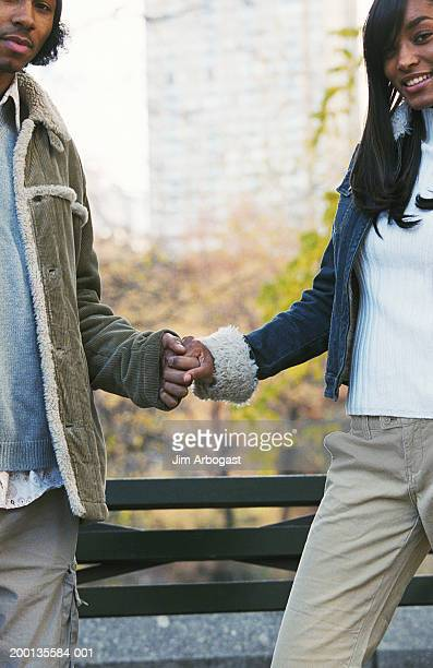 Couple holding hands in park, portrait