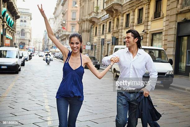 Couple holding hands in street