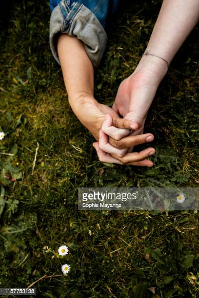 LGBT couple holding hands in the grass