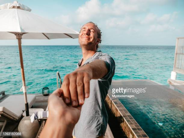 couple holding hands in the maldives - following moving activity stock pictures, royalty-free photos & images