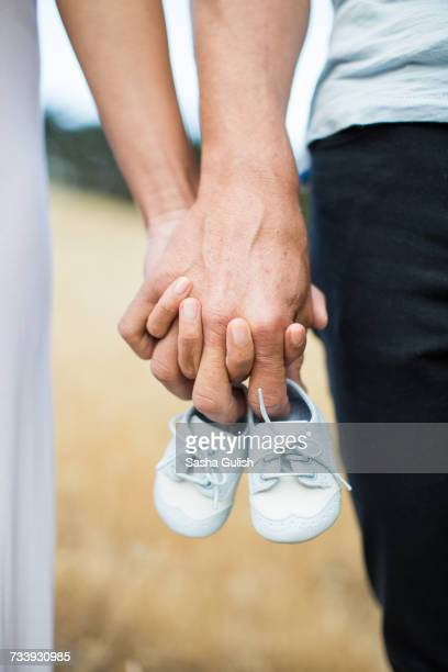 couple holding hands, man holding baby shoes on fingers, close-up - baby booties stock photos and pictures