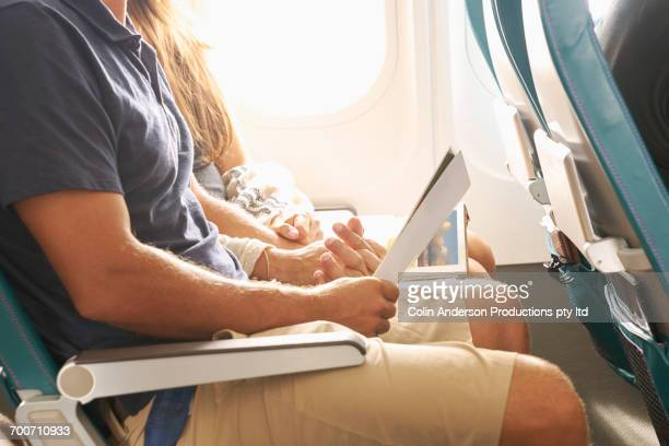Couple holding hands on airplane